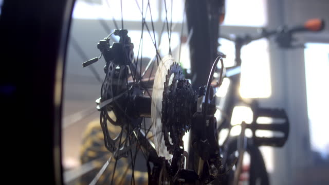 SLO MO LD Bicycle wheel turning as man is servicing the bike