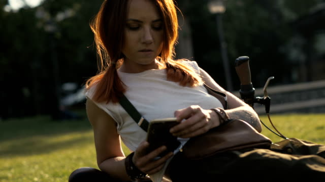 bicycle woman typing message on mobile phone in summer park - ragazza auricolari rossi video stock e b–roll