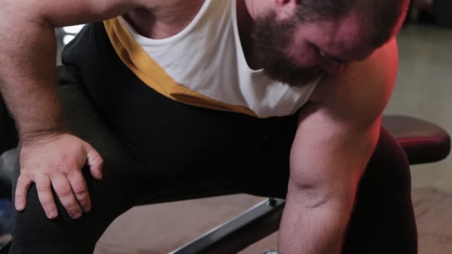 Big and powerful athlete trains dumbbell biceps in a sports club