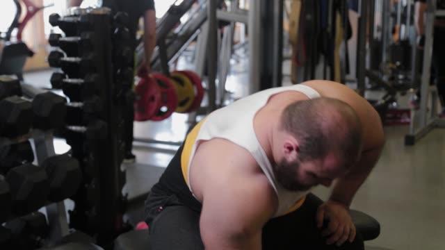 vídeos de stock, filmes e b-roll de atleta grande e poderoso treina bíceps de halteres em um clube esportivo - braço humano