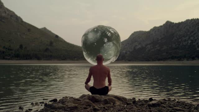 büyük top meditasyon adam önünde su gibi. - mountain top stok videoları ve detay görüntü çekimi