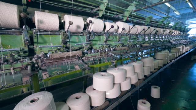 stora spolar roterar, buffrar trådar på fabriksmaskiner. - fiber bildbanksvideor och videomaterial från bakom kulisserna