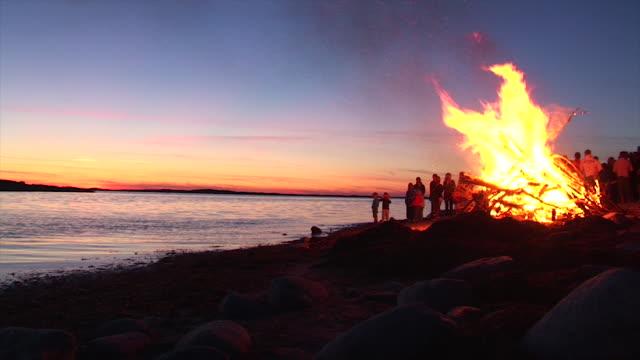 en stor brasa fest under en solnedgång på en strand vid havet.  barn som leker runt elden. - bohuslän nature bildbanksvideor och videomaterial från bakom kulisserna
