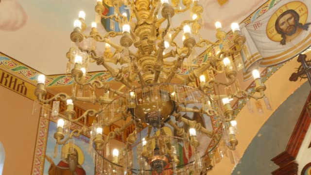 Big bronze chandelier in cathedral christian church, close-up Big bronze chandelier in cathedral christian church, close-up. victorian architecture stock videos & royalty-free footage