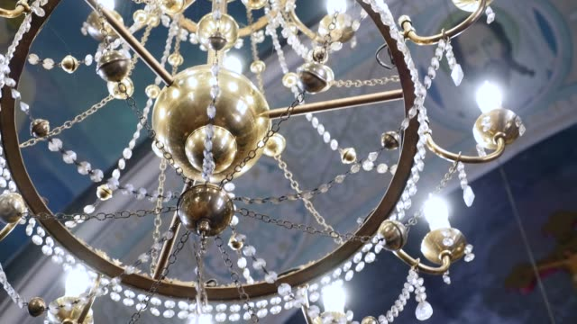 big bronze chandelier in cathedral christian church - candeliere video stock e b–roll