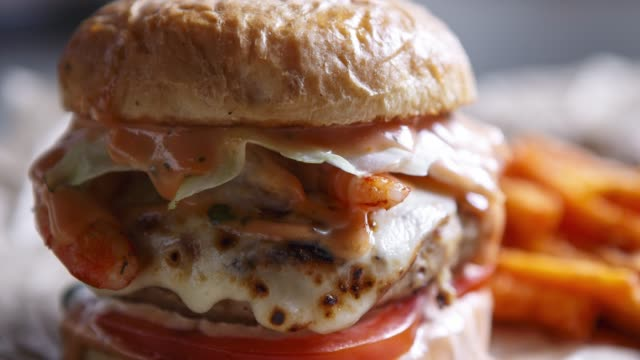 Big burger in close up Delicious big fat double hamburger.American fast food restaurant menu dish.Grilled huge burger with sauce,pork & burner cheese served on brown paper in cafe.Fast food close up menu stock videos & royalty-free footage