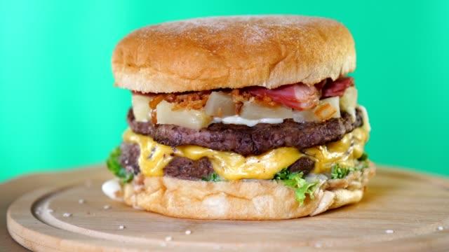 stor hamburgare med ost, sås och grönsaker är snabb roterande på en trä bräda framför grön skärm bakgrund. - hamburgare bildbanksvideor och videomaterial från bakom kulisserna