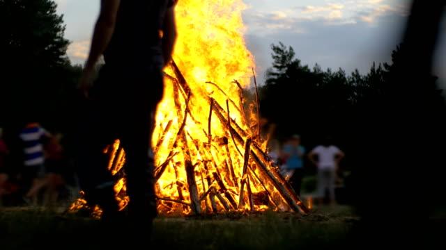 geceleri dalları yanık insanlar arka plan üzerinde ormanda büyük kamp ateşi - şenlik ateşi stok videoları ve detay görüntü çekimi
