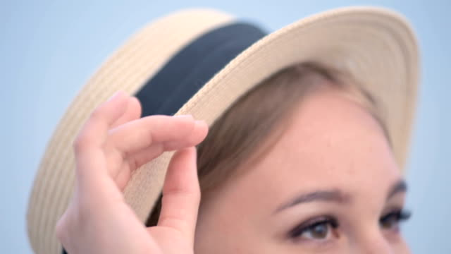 Big close-up face Portrait of an attractive caucasian young woman in a straw hat with pigtails straightens the hat with her hand looks away Big close-up face Portrait of an attractive caucasian young woman in a straw hat with pigtails straightens the hat with her hand looks away. charming stock videos & royalty-free footage