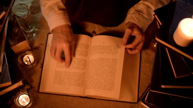 vidéos et rushes de magicien de fille gros gros plan dans une pièce sombre avec la chandelle à la recherche d'un sort dans un livre. caméra en direct clée faible. mystique. petit dof. découvre d'en haut - charmeur