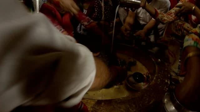 stor skara människor böja sig för att lingam heliga sten händer hälla vatten och mjölk sätta blommor prasad gamla hinduiska templet rishikesh timelapse - india statue bildbanksvideor och videomaterial från bakom kulisserna