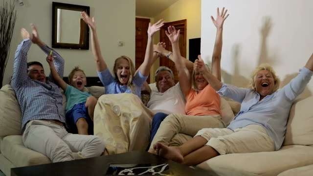 Big excited family watching sport game on TV video