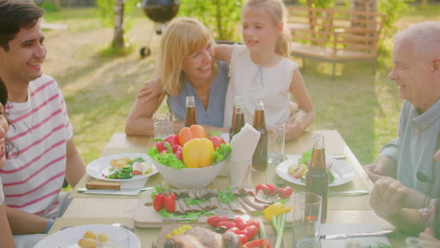 big family garden party celebration, gathered together at the table, eating, joking and having fun. gliding shot over the table. - reunion stock videos & royalty-free footage