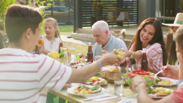 big family garden party celebration, gathered together at the table relatives and friends, young and elderly are eating, drinking, passing dishes, joking and having fun. - приём пищи стоковые видео и кадры b-roll
