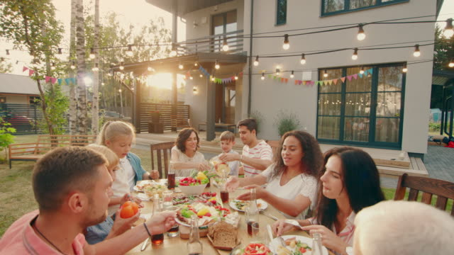Big Family Garden Party Celebration, Gathered Together at the Table Relatives and Friends, Young and Elderly are Eating, Drinking, Passing Dishes, Joking and Having Fun. Descending Top Down Camera Shot.