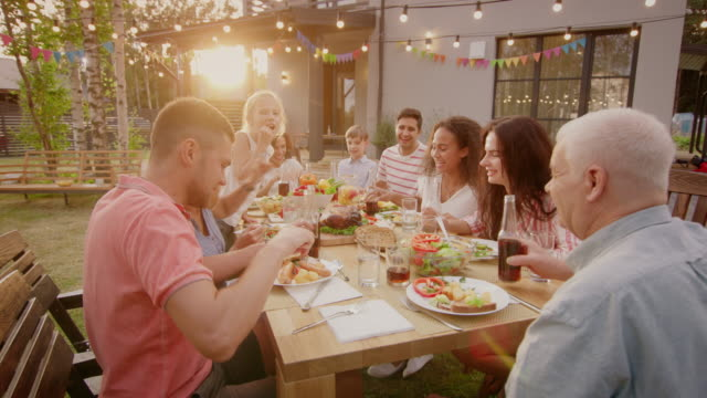 big family garden party celebration, gathered together at the table relatives and friends, young and elderly are eating, drinking, passing dishes, joking and having fun. - формальный сад стоковые видео и кадры b-roll