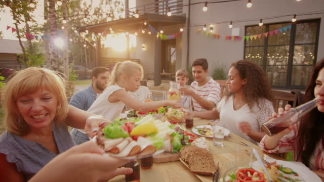 big family garden party celebration, gathered together at the table relatives and friends, young and elderly are eating, drinking, passing dishes, joking and having fun. - gardino video stock e b–roll