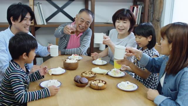 stockvideo's en b-roll-footage met grote familie met thee en cake - breakfast table
