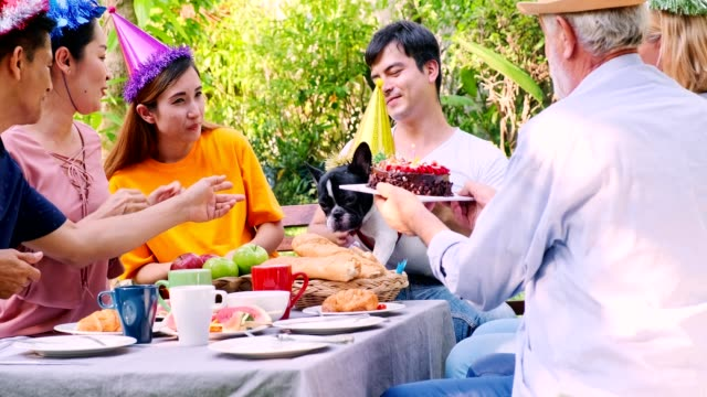 Big family reunion party outdoor. Giving cake to dog. Asian senior man, woman, Caucasian man and woman, pregnant woman. Big family reunion concept, summer time.