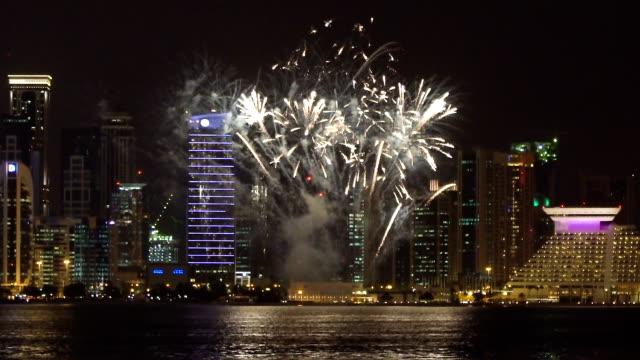 vidéos et rushes de grand feu d'artifice dans la ville moderne de nuit - doha