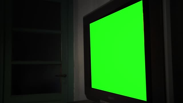 Big Flat Screen Tv With Green Screen In A Dark Room. Zoom In.