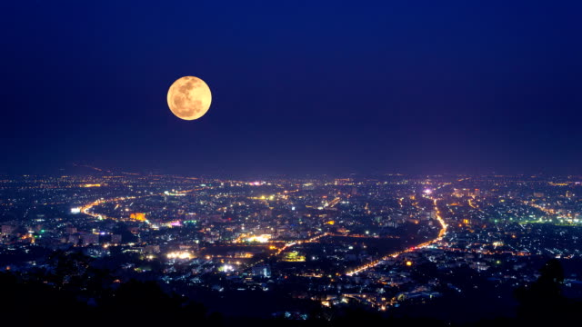 big full moon moving over downtown (time lapse) video