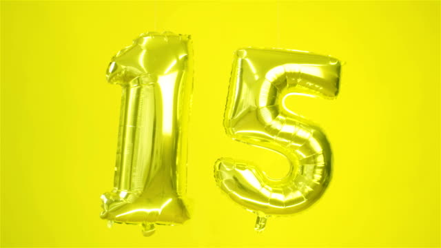 big golden ball of number fifteen on a yellow background. - anniversario video stock e b–roll