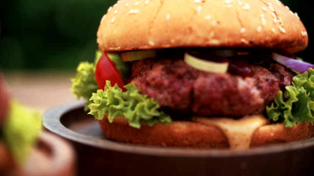 Big gourmet burger with fresh ingredients and prime beef patty video
