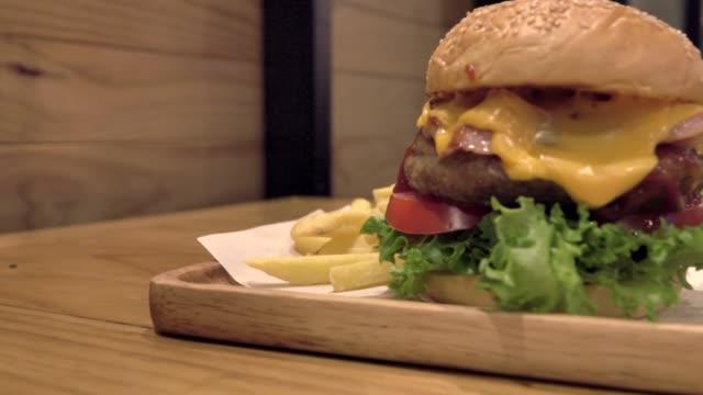 vídeos de stock e filmes b-roll de big gourmet burger with fresh ingredients - fast food