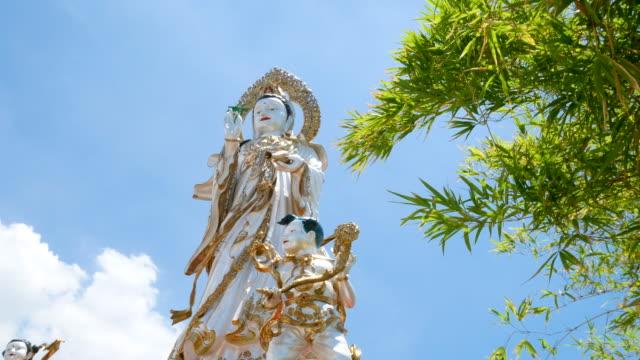 grande statua di guanyin con cielo blu, risoluzione 4k. - pathum thani video stock e b–roll