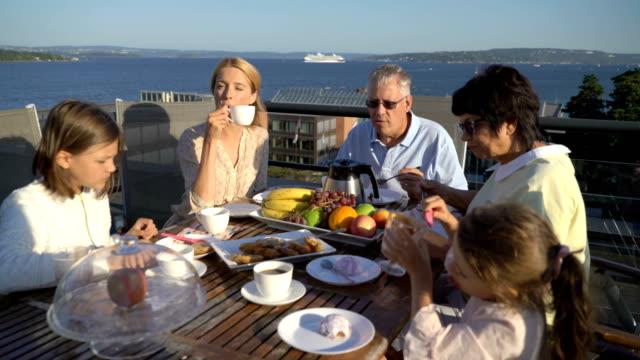 eine große, glückliche familie hat abendessen auf der terrasse auf dem dach des hauses. - brunch stock-videos und b-roll-filmmaterial