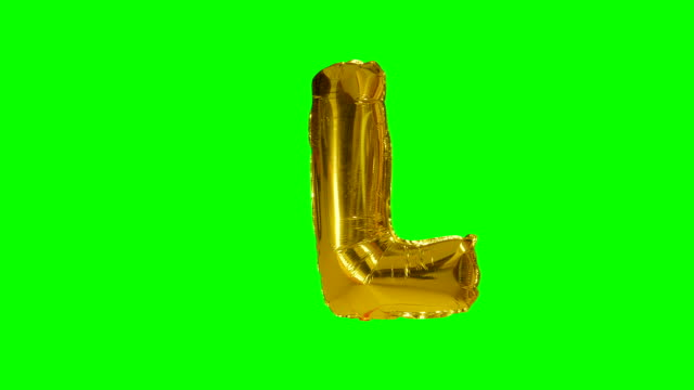 big letter l from alphabet helium gold balloon floating on green screen - wielka litera filmów i materiałów b-roll