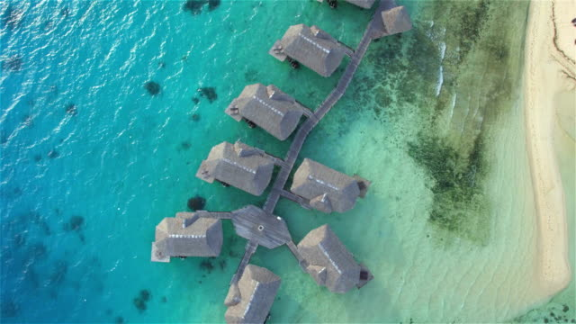 AERIAL: Big luxury oceanfront hotel with deluxe overwater villas and secluded beachfront bungalows nestled in the beautiful blue lagoon, with lush tropical landscapes and white sandy beaches. Perfect romantic getaway or dream honeymoon video