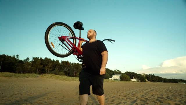 Big Man Carries A Bike On His Shoulders video