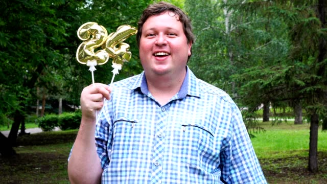 big man holding golden balloons making the 24 number outdoor. 24th anniversary celebration party - 20 24 anni video stock e b–roll