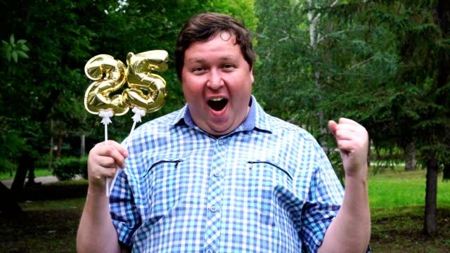 großer mann hält goldene luftballons machen die 25 nummer im freien. 25-jahr-feier - zahl 25 stock-videos und b-roll-filmmaterial
