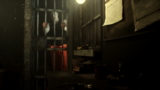 Big men standing at door in prison cell holding prison bars video