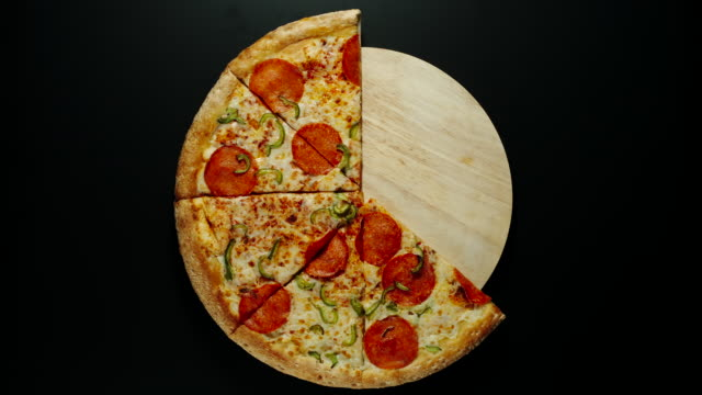CLOCKWISE: Big Pizza Is Eaten Up On The Wooden Board, Black Background