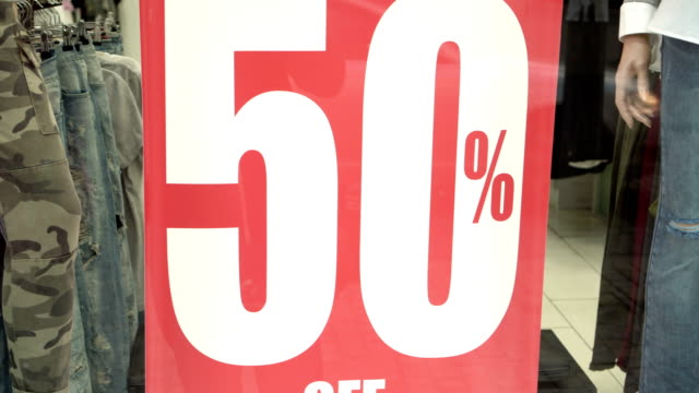 Big red sales sign in a shop window. 50 percent sales. Promotion. Consumerism concept video
