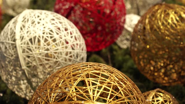 Big round holiday balls hanging on huge Christmas tree outdoors.