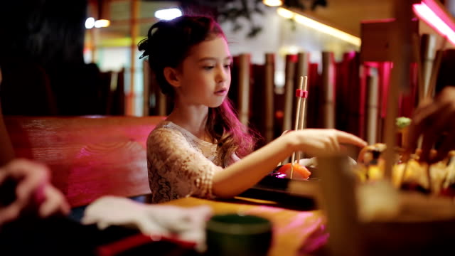Big set on sushi and rolls on the restaurant plate. Family dinner at pan-Asian restaurant. Little girl eating rolls with chopsticks video