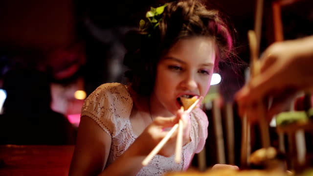 Big set on sushi and rolls on the restaurant plate. Family dinner at pan-Asian restaurant. Girl eating rolls with chopsticks video