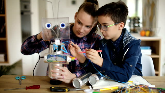 big sister and little brother constructing a robot together - brother stock videos and b-roll footage