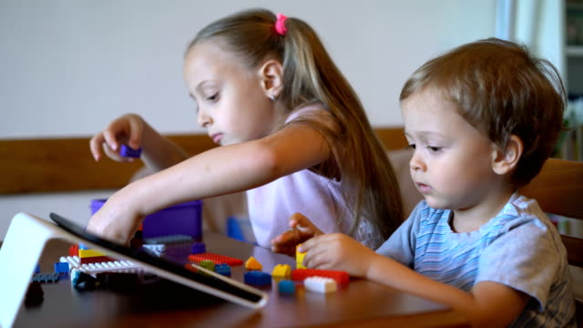 Big sister and little brother playing with plastic bricks at home video