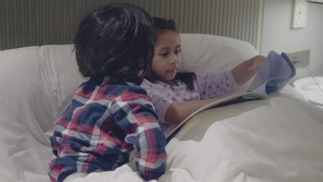 彼らのアパートで小さな男の子におとぎ話を読むビッグシスター - 兄弟姉妹点の映像素材/bロール