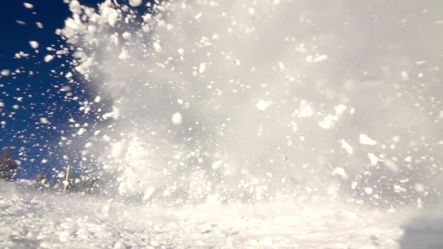 SLOW MOTION: Big snow avalanche sliding down a mountainside and into camera
