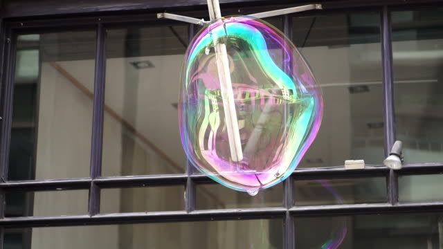 Big soap bubble being made and floating in the air then explode in slow motion 120 fps video