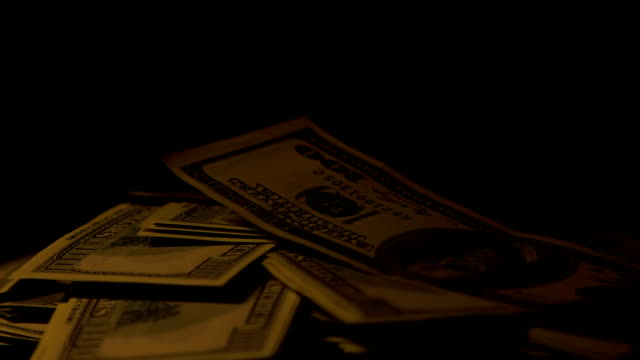 Big sum of dollar cash in dark place, ransom for kidnapping hostage, close-up