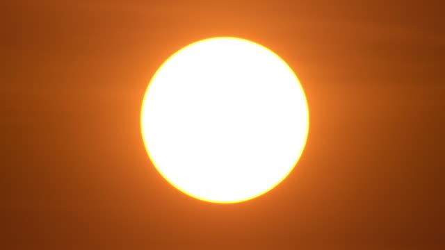 4k big sunset nahaufnahme zeitraffer in orange farbe - sonne stock-videos und b-roll-filmmaterial