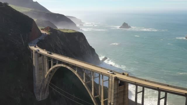 vídeos de stock, filmes e b-roll de ponte big sur. bixby. rota 1. rota do estado da califórnia. oceano atlântico. drone aéreo. - ponte